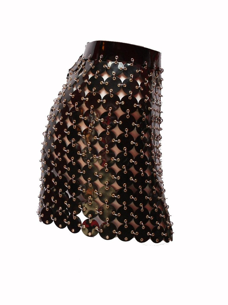 The edgiest skirt in the world is this black vinyl chainmail skirt by Paco Rabanne with gold hardware. Snaps up the back. Unworn condition with original tags still attached! Size 38  Original Price $2,350