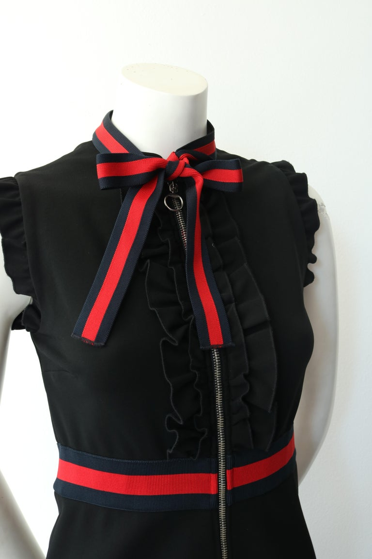 -The dress is further enhanced by knitted Web trim on the waistband and on the neckline knotted into a decorative bow.  -Black compact viscose jersey with blue and red knitted Web detail.  -Ruffle detail on front placket and sleeves.  -Front zip.