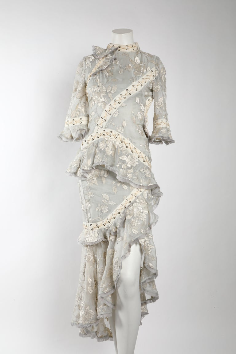 Beautiful feminine yet modern Zimmermann Eyelet trimmed gown with tiered ruffles.   This could be a bridal gown or just for an event. Colors are light grey, cream and white. The silhouette and dress itself feels like a corset, which makes it