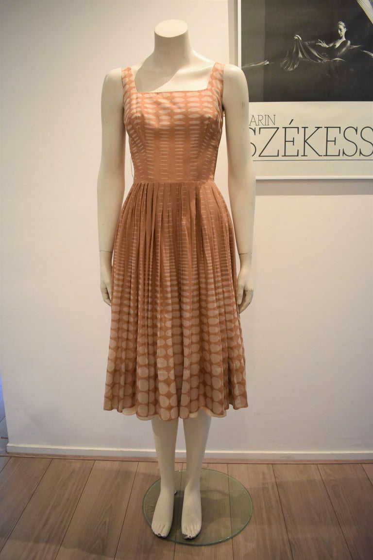 This lovely dress is made from batiste (a lightweight, semi-sheer cotton fabric) and it has a salmon slip dress underneath. The dress has a very tiny waist (the zipper could not completely close on the mannequin). The dress has 2 very thin belt