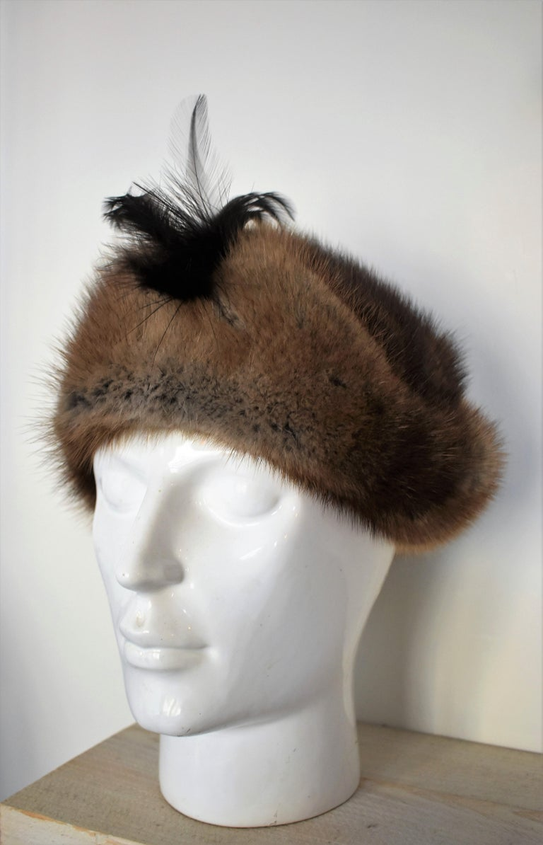 This warm and very fluffy fur hat is in great condition. The fur has beautiful shades of grey and brown and the front of the hat is decorated with feathers. A beautiful accessory to keep you warm.