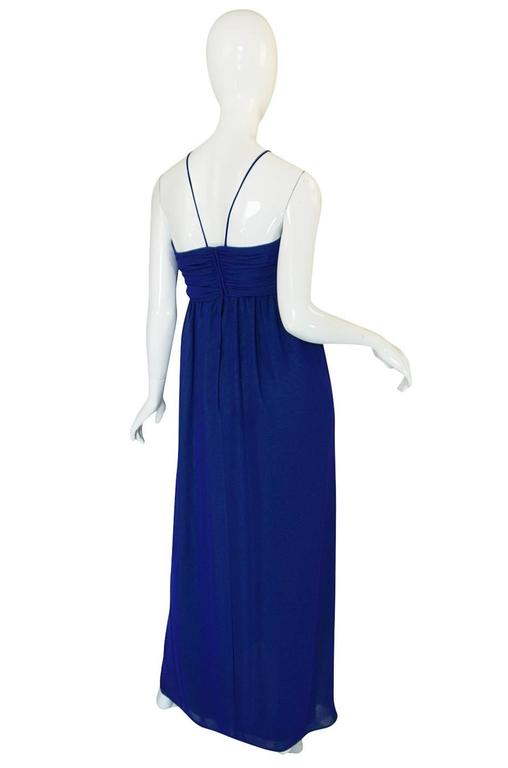 This Adele Simpson dress is wonderful and so pretty once on. The dress is made from layers of a royal blue chiffon that has a pretty panel of contrasting green that runs down the front to create a ruffle effect. The bust is given shape and detail by