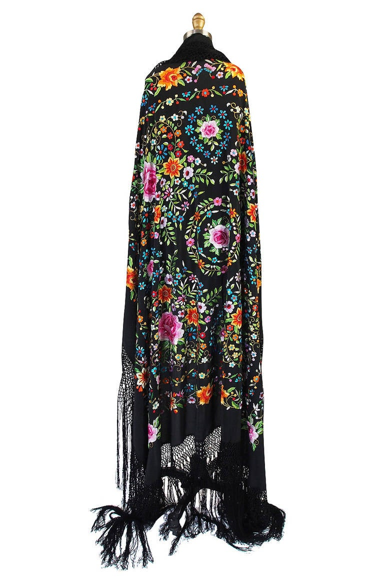 A spectacular and huge embroidered silk Chinese export shawl from the twenties.The floral design is particularly bright and vivid and offset by that black silk backdrop. The embroidered design of flowers is very beautiful and in a myriad of colors.