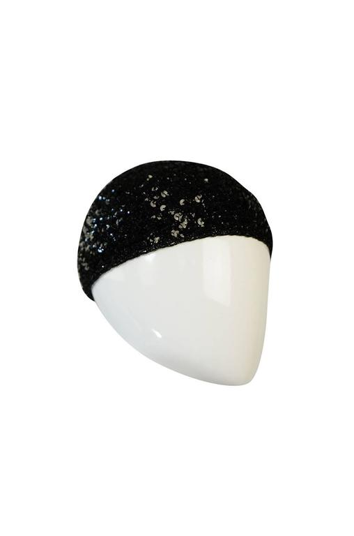 These are so hard to find and this is a fine example. The Halston sequin cloche was a mainstay of the Studio 54 set. Bianca Jagger famously wore a red beret version but this one is the more fitted cap design. It is made of a stretch lurex knit upon