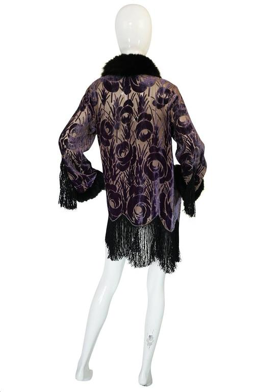A showstopping 1920s cut silk devore jacket that is really a work of art. The body of the jacket is completely covered with A silk velvet, stylized floral design that is applied over a silk crepe base. The effect of that dusky lavender against the
