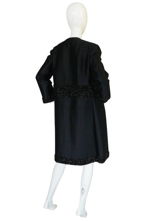 This is a beautiful coat with very fine workmanship and beautiful construction. The black makes it is appropriate for just about any occasion and the cut is simple and sleek. It is made from a fine and heavy black silk and the cut is almost severe