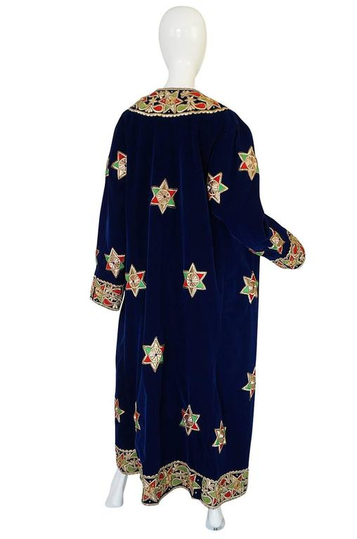 This is a magical coat and very unique. It is made from a beautiful royal blue velvet that has an extraordinary amount of embroidered applique work scattered over its surface and defining the edges and cuffs. These are bright and colorful and edged