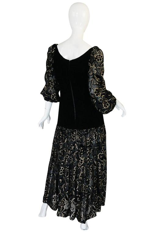 This dress is quintessentially eighties and the lines pure Yves Saint Laurent during this time period. It is made from a combination of a inky black velvet through the body with a gold flowers in a black silk chiffon adoring the sleeves and skirt.