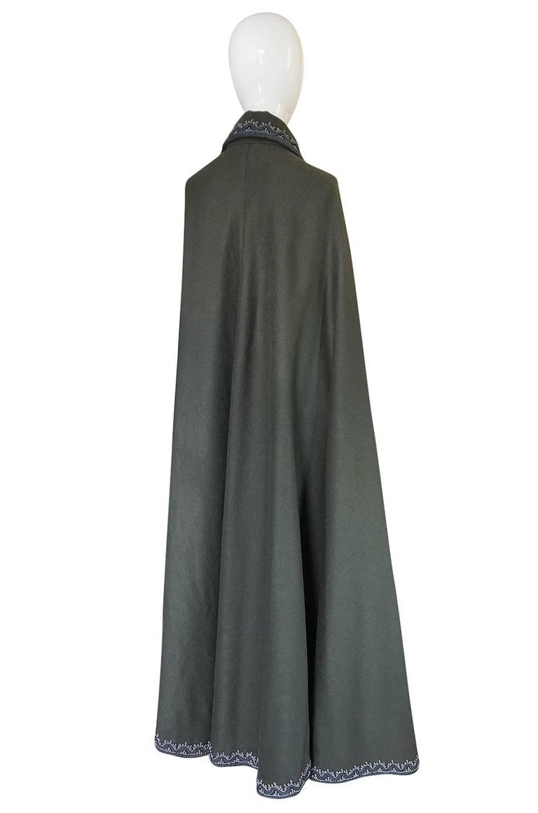 This is a superb cape that is made from a grey wool and is cut to be full length and will tremendous volume through the cut. The lines are easy and the weight of the wool allows it to fall from the shoulders in a swoop of fabric that falls to the