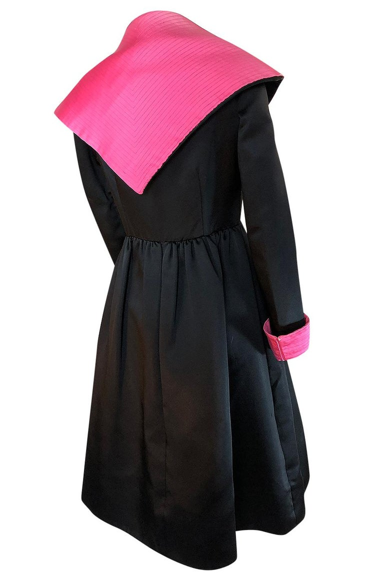 This Geoffrey Beene wrapped coat is fabulous with its bright contrast of that hot pink silk satin against the heavy black silk base. The collar, cuffs and the inner edge of the coat are finished with  a vivid pink and that shot of bright color