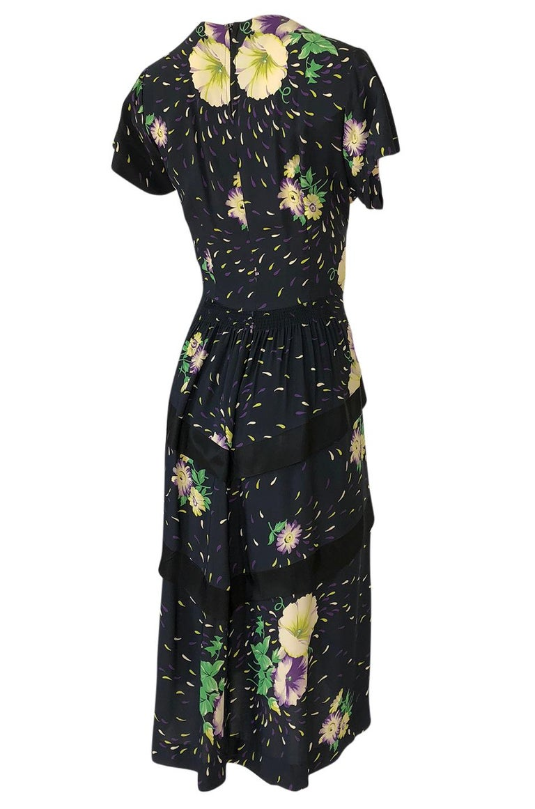 This absolutely fantastic silk swing dress from the 1940s has a vivid and stunning, hand painted floral print that covers it head to toe. The floral design that covers the dress feels pretty and feminine and the colors still feel as crisp and