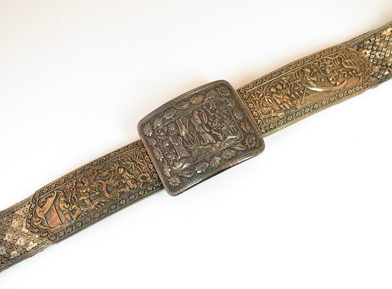 Offered here is an early 19th century Asian silver belt of tightly-woven flat dense geometric mesh embellished with a crisscross design of tiny floral studs. The large rectangular curved buckle is flanked by two large gold-washed elongated panels,