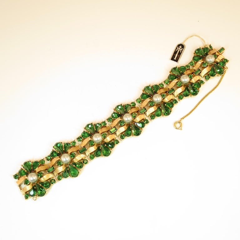Offered here is a Crown Trifari Alfred Philippe-designed heavily-gilded rhodium bracelet embellished with emerald Swarovski crystals and silver glass pearls from the 1950s. The heavy link design presents slightly domed stations in a flowing