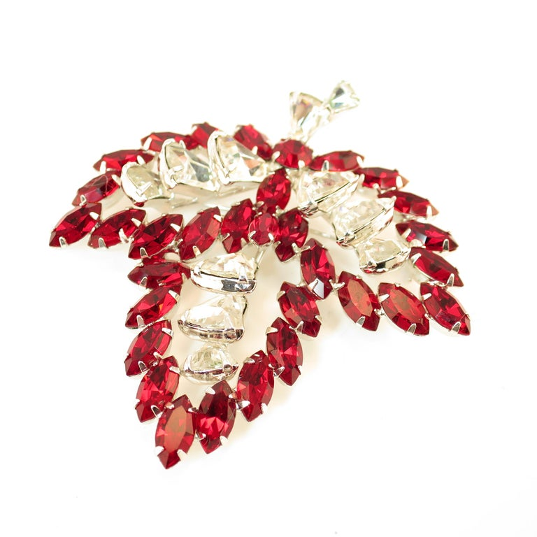 Offered here is a Vendome rhodium-plated brooch embellished with Austrian crystals from the 1950s. The three-dimensional tripartite leaf design presents deep-ruby marquise stones outlining the leaf, surrounding a center of fancy-cut bell-shaped
