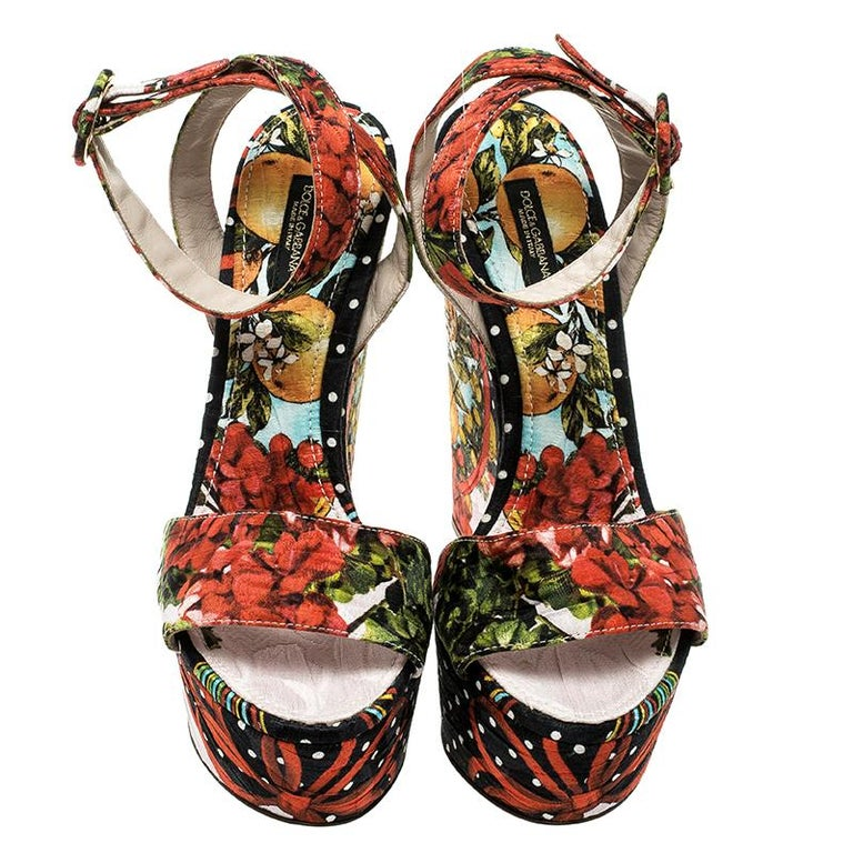 Embrace quirky fashion with this pair of sandals from the house of f Dolce and Gabbana that has been designed to bring out your inner fashion diva to the limelight. Enhanced by a vibrant floral design, these wedge heeled sandals have a peep-toe