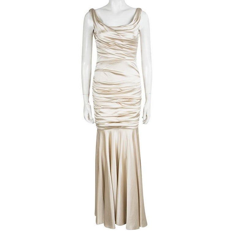 It's time to cast a spell and make others go gaga with this flawless gown from Dolce and Gabbana. The sleeveless gown in a shimmering beige shade is made of a silk blend and features a satin ruched silhouette with pleat detailing. It comes with a