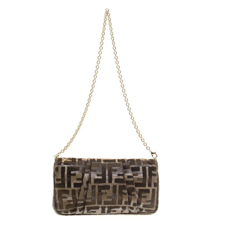 Look glamorous while carrying this shimmering Zucca Baguette chain clutch by Fendi. Crafted from metallic Zucca glitters, it features a front flap with the notable Fendi logo in gold-tone that opens a roomy interior lined with dark brown fabric and