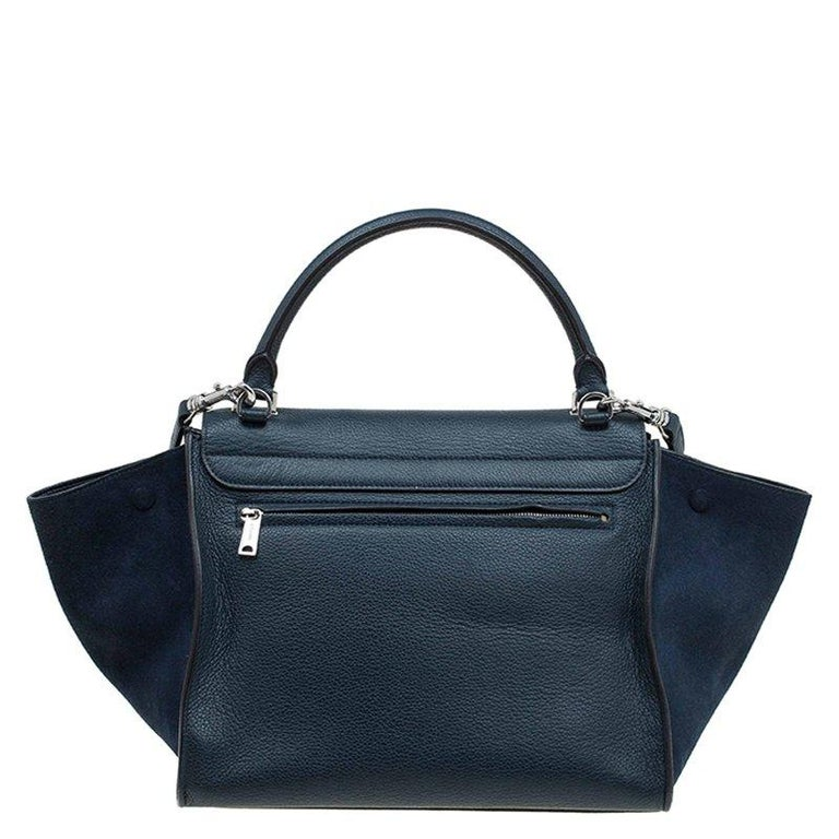 The instantly recognisable 'Trapeze' bag from Celine is a gorgeous addition to your wardrobe. This medium Trapeze bag is crafted from leather and suede in a navy blue shade. The iconic wing style in luggage-tote, a rolled up top handle and a