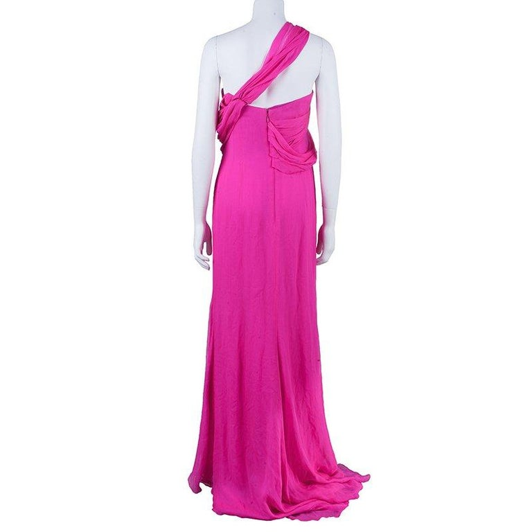 This fairy tale draped gown in a hot pink shade from Oscar de la Renta is a breathtaking one! This one-shoulder dress features a pleated shoulder strap falling at the back creating a unique style. The pleated bust drape highlight and a side fall add