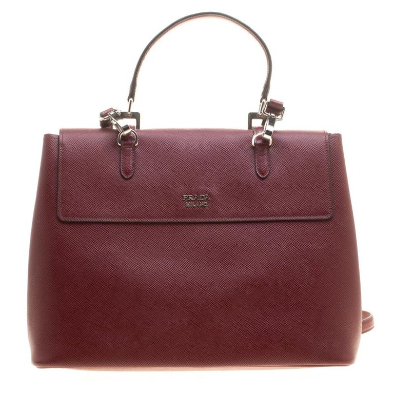 Prada is defined by its exalted craftsmanship, and this burgundy top handle bag is a true testimony of their flair. This bag is an elegant combination of style, sophistication, and structure. The Saffiano Lux leather exterior is paired with belt
