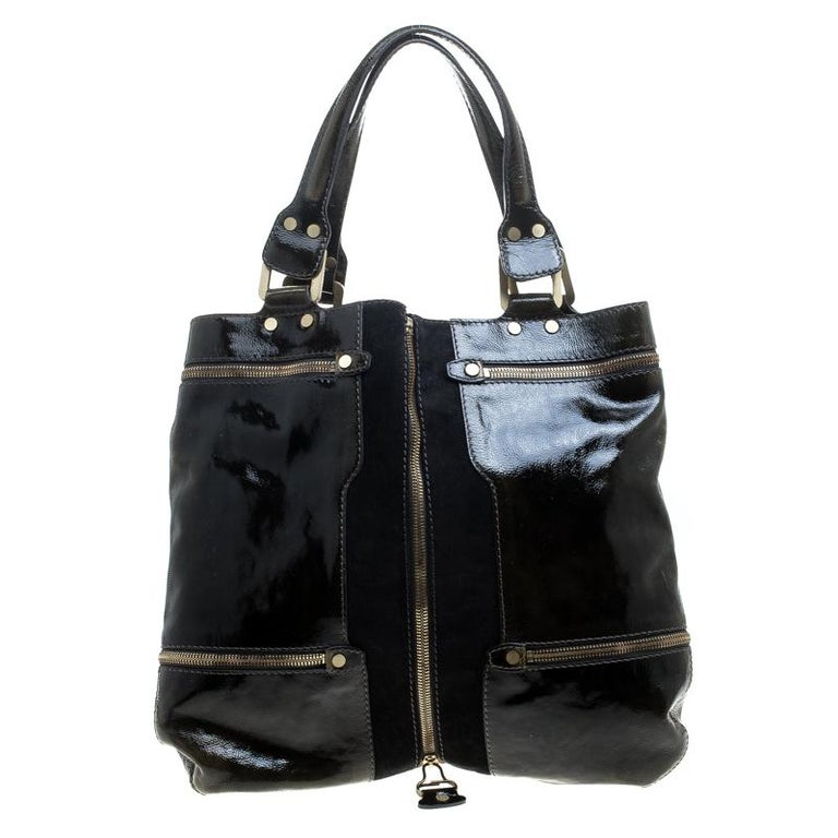 Easily shift from day to night with this one in functional patent leather exterior detailed with a suede panel and chain accents making this Jimmy Choo creation a premium design. As magnificent and rare it looks from outside, it has an equally