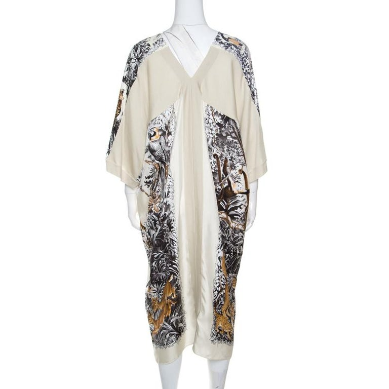 This cream tunic dress from Hermes is made of silk and cashmere and features a lovely Jungle Love printed pattern all over it. It flaunts a round neckline, short sleeves and a deep back. Pair it with smart platform sandals and a leather clutch to