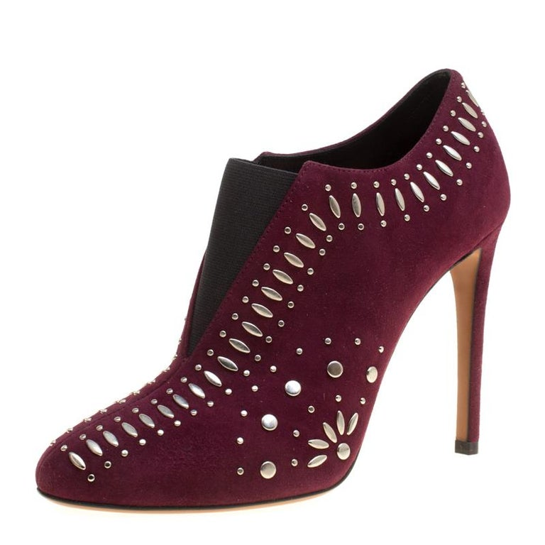 Breathtakingly beautiful are these booties from Alaia! The burgundy booties are crafted from suede and elastic bands and features round toes, multiple silver-tone studs adorned all over the exterior, comfortable leather lined insoles and 11 cm