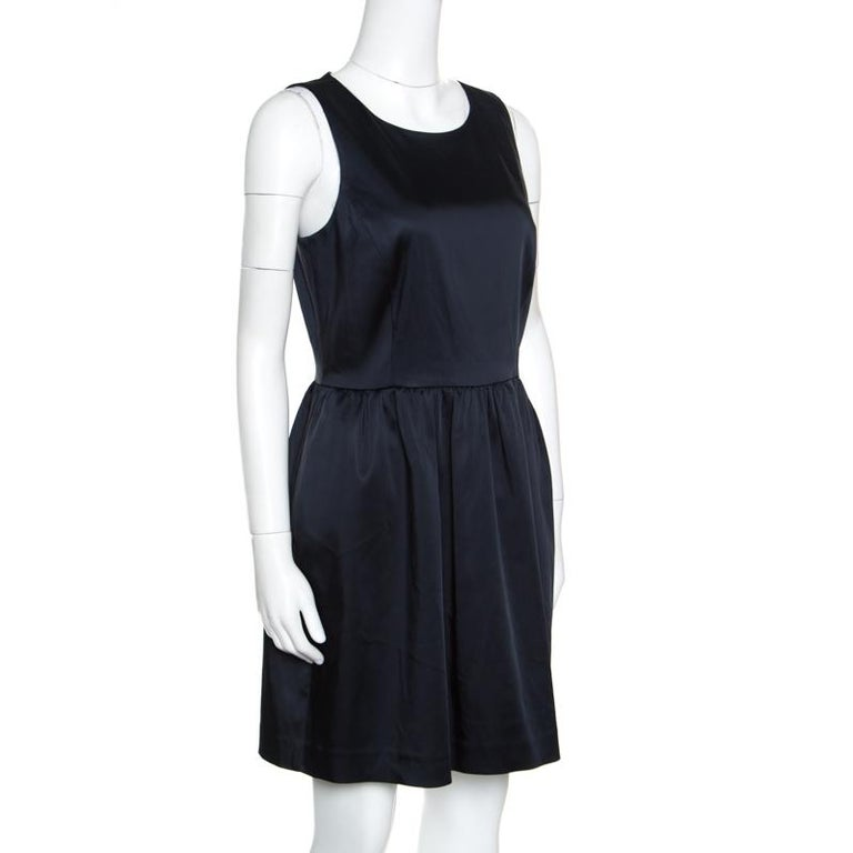 This sleeveless sheath dress from Armani Collezioni is sure to make you stand out and win praises wherever you go! The navy blue creation is made of a blend of fabrics and features a round neckline, a pleated silhouette below the waist and a