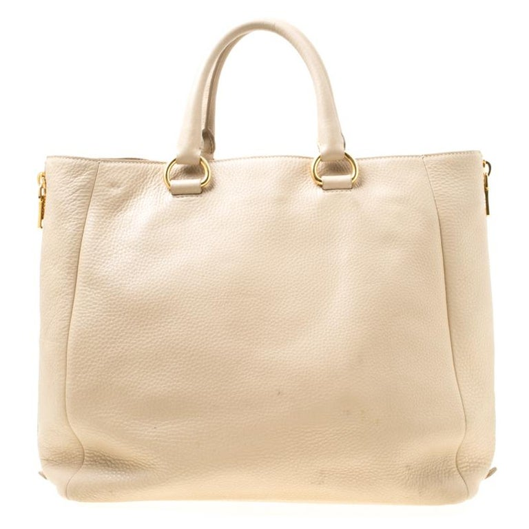 Prada brings you this tote that is overflowing with style. Covered in beige, the bag brings a spacious nylon interior to dutifully hold all your necessities and side zippers which can be unzipped to accommodate more things. Leather made, the bag is