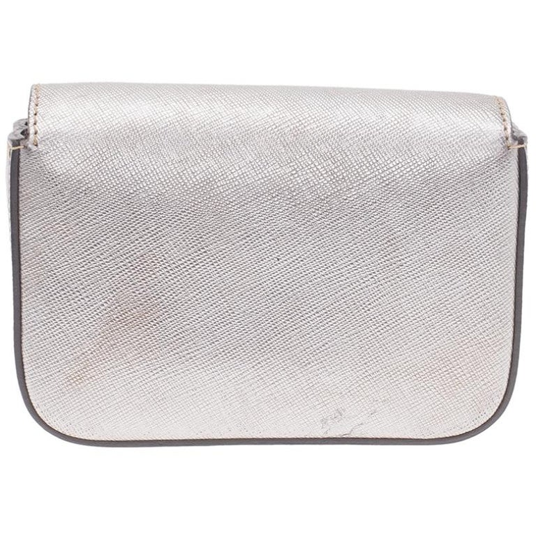 Grab this feminine and fun Mini Box clutch by Prada before it's too late! It is crafted from silver Saffiano leather and features gold Prada name sitting at the front flap. Secured with a snap button closure, the flap opens to a fabric lined