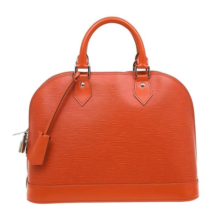 The original design of the Alma bag designed by Gaston Vuitton himself and named after the Alma bridge in Paris. This Louis Vuitton Alma PM bag is made from Epi leather in a bright orange shade. It features two rolled, top handles and silver tone