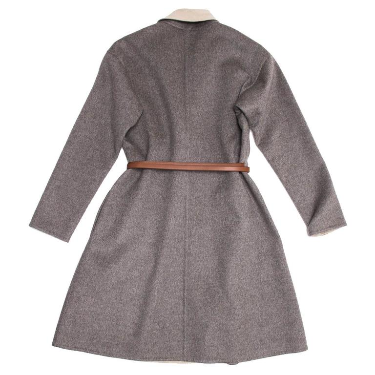 Cashmere A-line coat with heather grey outer layer, tan color lapel and inside layer. The finishing of the fabric is double face, which gives it a very clean and elegant look. A tan brown leather belt is to be wrapped around the waist and fastened