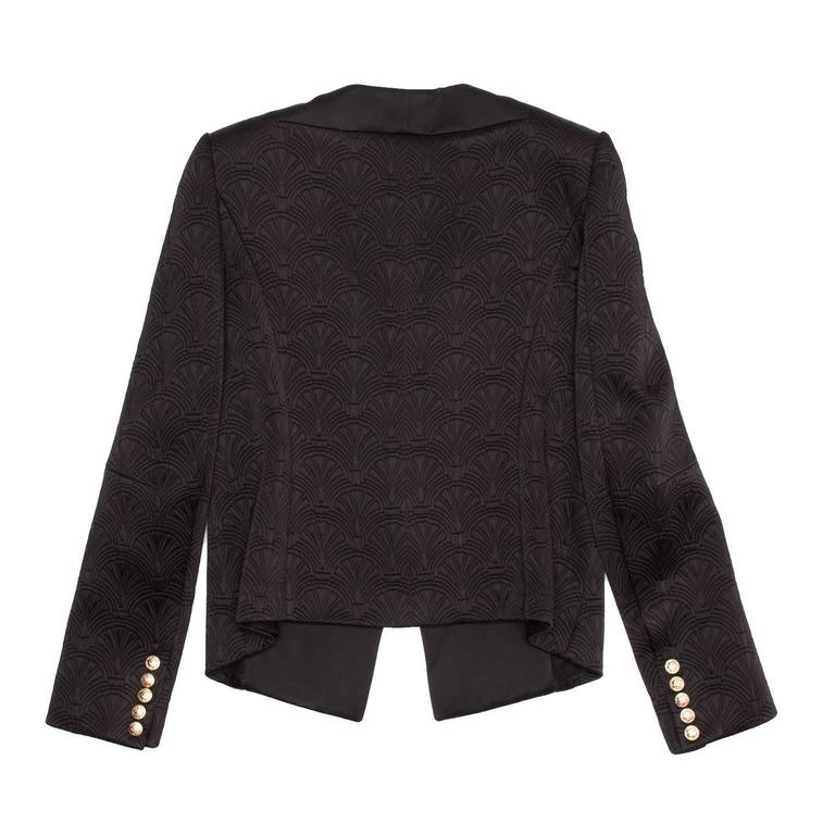 Black shell pattern jacquard tuxedo jacket. It's a fitted and cropped style with a long satin lapel ending at waist, where the jacket fastens with an invisible hook. The cuffs are embellished with five beautiful gold snap buttons. Made in