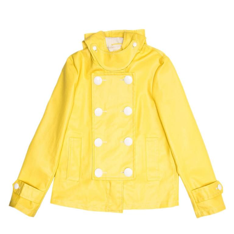 Bright yellow rain slicker sailor style jacket with a cropped trapeze fit and big white buttons on a double breast front panel. Under the buttoned panel the front fastens with a chunky white metal zipper, while smaller white round buttons adorn