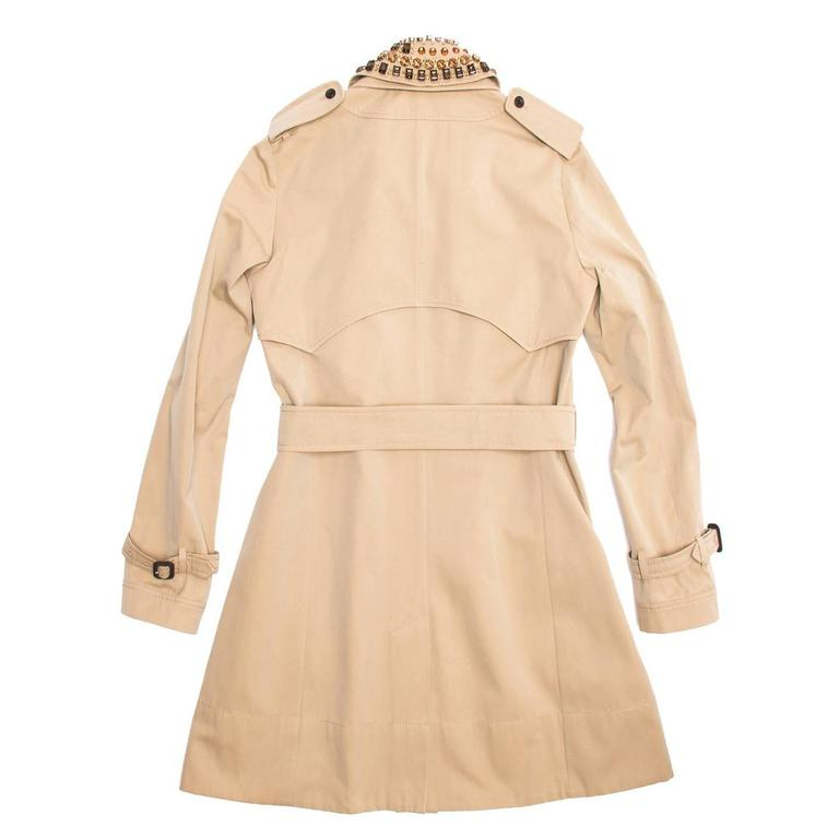 Classic knee length khaki cotton trench coat with belted waist and detachable jewel embellished collar. The front is single breasted and fastens with brown buttons like the smaller ones on the pockets. The cuffs are belted as well and enriched with