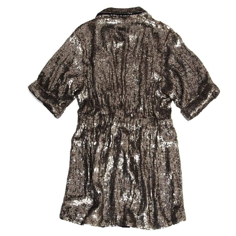 Stunning matt silver fully sequined dress coat with double breasted front closing, slightly gathered waist and short sleeves with turn-ups. The dress has a blazer collar with small lapel, flap pockets and it can be worn as a long jacket too. The