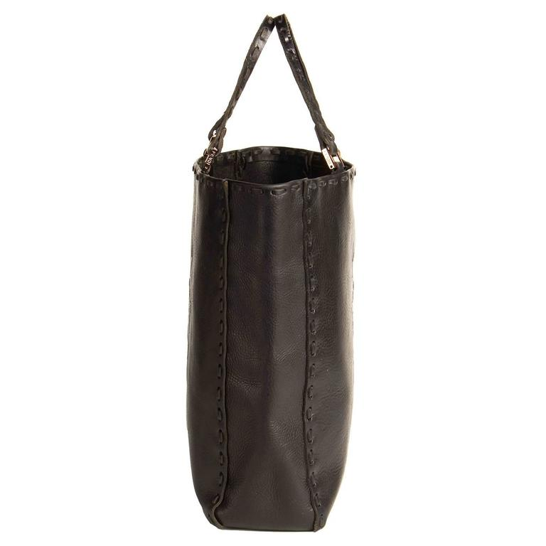 Black leather tote bag with beautiful crowns and antlers embossed design on front and back, while all edges of the bag and handles are enriched by thick leather top stitches. The handles are attached with elegant rectangular copper buckles, while a