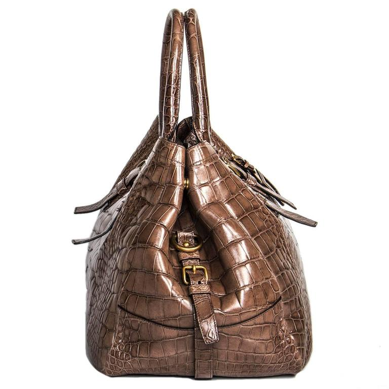 Grey/brown beautifully crafted crocodile large bag with Prada brushed gold metal letters. Front, back and sides are also enriched by buckles and straps detailing. A gold metal snap fastens the bag as well as the sides to make the bag wider. Special