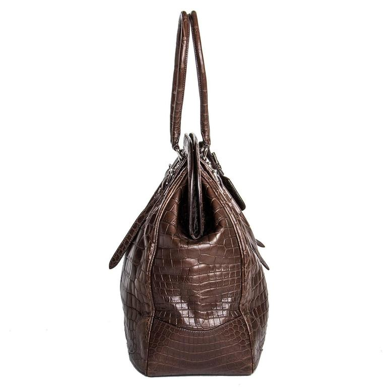Chocolate brown crocodile bag with a vintage classic design, style reference number BR 3511. Front and back are enriched by extra straps with little belt buckles and pleats that emphasize the round volume of the bag. The front of the bag is also