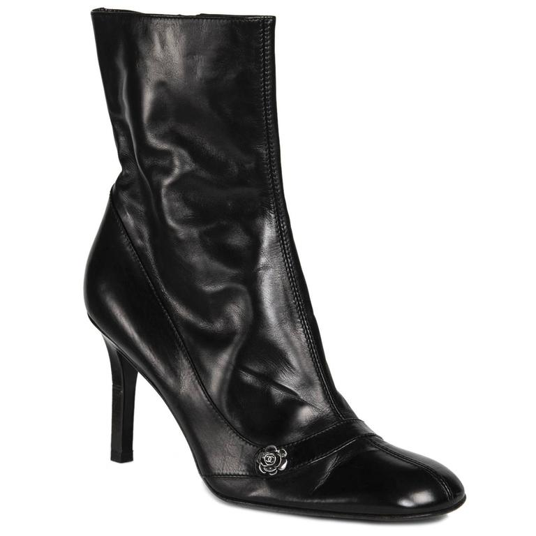 Black leather round toe boots with a leather insert at front and sides. A little metal camellia flower is attached to the insert on the front insert. The zipper is in the instep and the interior of the shoes is dark brown. Heel 3.5