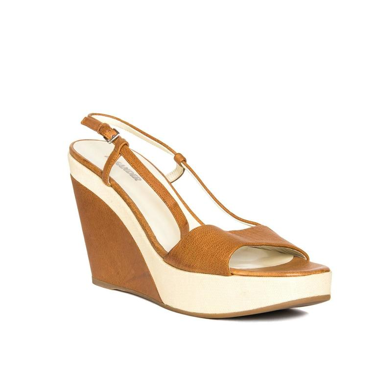 Warm cognac brown leather wedges with open front and sling back that fastens with a brushed silver buckle. The beige thin rattan that covers the platform continues under the heel creating a beautiful detail, while the rest of the wedge is covered in