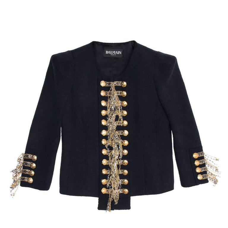Blue silk & cotton woven cropped jacket with gold and silver chains to create a unique military style statement detail. The neckline is round and elegant and the jacket fastens with invisible hooks at center front where the dangling chains meet