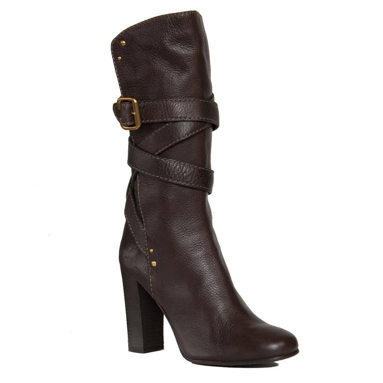 Chocolate brown calf high leather boots with round toe and wrap around straps that fastens on the side with a brushed gold color buckle. Round gold studs and thick tone-on-tone stitches decorate the boots further. Made in Italy. Heel 4