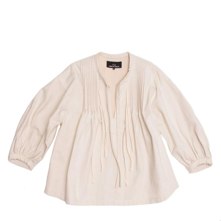 Natural color thick cotton cropped blouse with fixed pleats at top front that create an A-volume. The top is collarless and the biding on its edge ends hanging at the front. More thin ribbons dangle at the front opening. The armhole is wide and