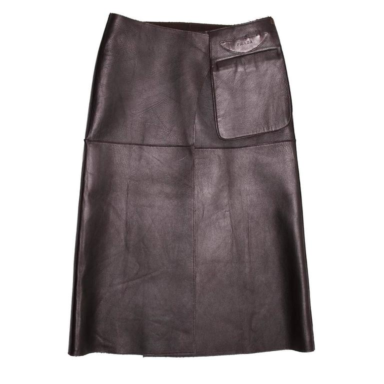 Dark brown leather reversible skirt with chocolate brown camel hair inside. It is a high waisted skirt with a wrap closure and a pouch pocket detail embellished by a Prada logo on the leather side.