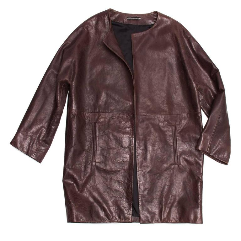 Burgundy lambskin leather coat with round collar and dolman sleeves. The fit is boxy and mid-length; the front is open and buttonless and enriched by two vertical welt pockets at lower waist. Made in France.  Size  42 French sizing  Condition
