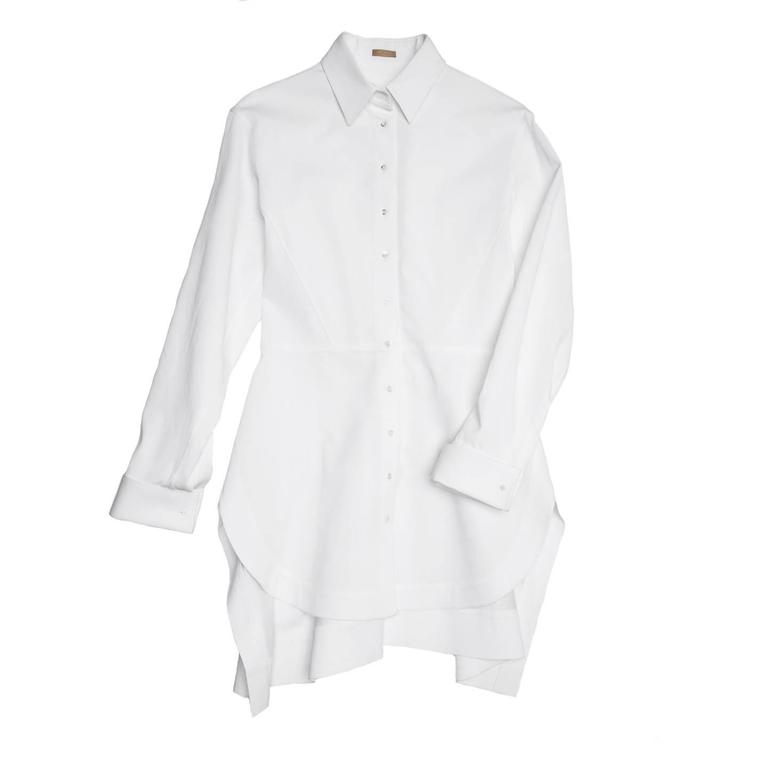 White thick cotton twill long shirt with peter pan collar, peplum waist seam at front and belt insert at back. The skirt part is flared and both the back body and skirt are ruched. The front hem is round while the back is squared; the cuffs are