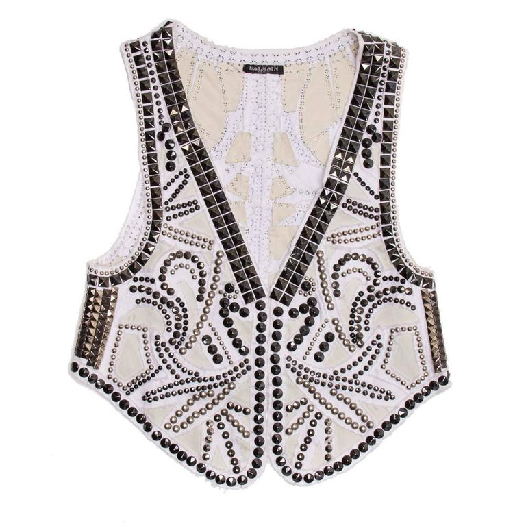 White denim vest with all over silver and gun metal studded design.