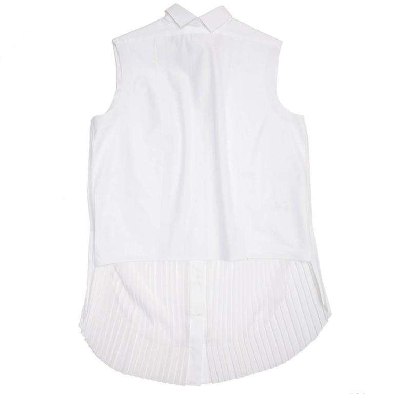 White shirt with a small peter pan collar with points at central back to duplicate the front. The back body is fitted, short and made of pure cotton. The front top part is made of a double layer of cotton to create rigidity, as well as the button
