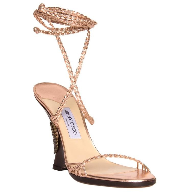 Metallic pink copper color leather braided sandals with open front and lace up ankle long straps. The dark brown wood wedges are enriched by a bronze medallion and the copper leather strings before they braid. Vero Cuoio. Made in Italy. Heel